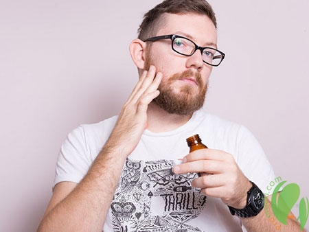 мужчина наносит масло на бороду