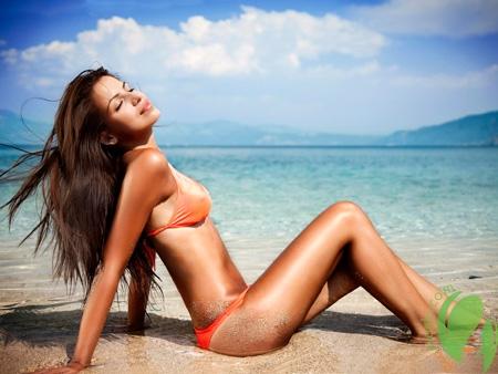 девушка загорает с солнцезащитным кремом